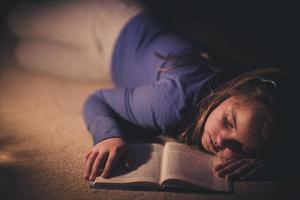 Mädchen, das Buch in der Beleuchtungslampe liest