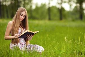 Studentin sitzt auf Rasen und liest Lehrbuch.