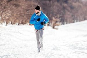 Mann läuft und trainiert an einem schneebedeckten Wintertag