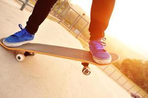 Beine in Turnschuhen auf einem Skateboard