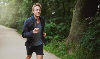 gesunder Mann in der Jacke, die am Park joggt foto
