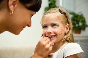 Frau malt das Gesicht eines Kindes für den Urlaub foto