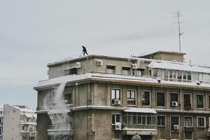Bucharest, Rumänien, 2020 - Mann schiebt Schnee vom Dach