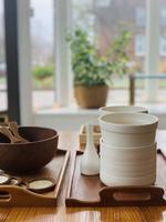 weiße Keramikschalen auf einem Holztablett foto