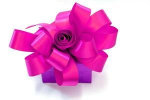 Geschenkbox gebunden mit einem rosa Band lokalisiert auf weißem Hintergrund foto