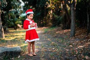 asiatisches Mädchen im roten Weihnachtsmannkostüm foto
