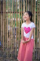 Porträt des glücklichen asiatischen Mädchens, das im Park steht foto
