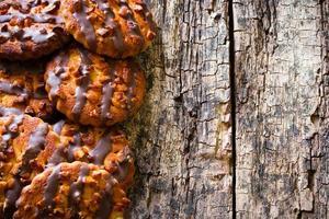 köstliche Kekse mit Schokolade und Nüssen auf einem hölzernen Hintergrund foto