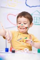 Porträt eines niedlichen Jungen, der mit Farben spielt foto