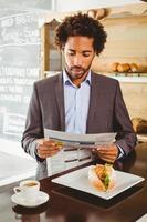 Geschäftsmann liest Zeitung beim Mittagessen foto