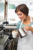 hübscher Barista gießt Milch in eine Tasse Kaffee