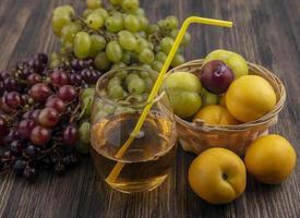 Traubensaft mit Früchten auf hölzernem Hintergrund