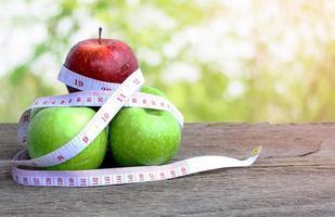 roter Apfel und grüner Apfel mit Maßband foto