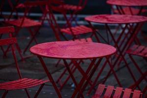 rote Tische und Stühle nass vom Regen