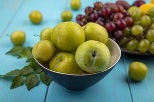 frische Früchte auf blauem Hintergrund mit Blättern verziert foto