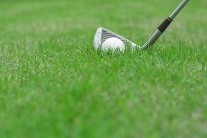 Nahaufnahme eines Golfballs auf grünem Gras im Golfplatz