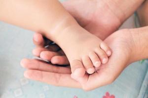 Mutters Hand wiegt den Fuß eines Babys