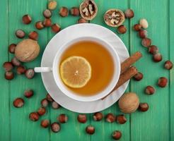 Lebensmittelfotografie flache Lage einer Tasse Tee mit Nüssen auf hölzernem Hintergrund
