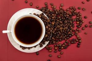 Lebensmittelfotografie flache Lage einer Tasse Kaffee und Kaffeebohnen auf rotem Hintergrund