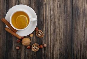 Flache Lage der Lebensmittelfotografie einer Tasse Tee mit Nüssen und Zimt auf hölzernem Hintergrund