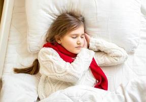 süßes Mädchen im Schal und im Pullover, die am Bett schlafen