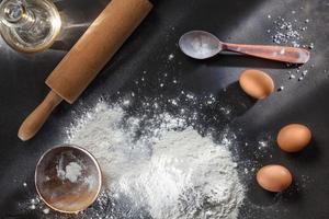 Mehl und Zutaten auf schwarzem Tisch foto