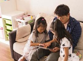 kleine Mädchen und eine Tablette mit den Eltern foto