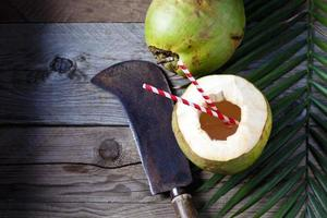 Kokosnuss mit Trinkhalmen, Hackmesser auf Holz foto