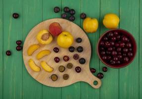 verschiedene Früchte auf Schneidebrett und grünem Hintergrund