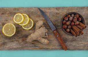 Zitrone und Ingwer mit Gewürzen auf Holzbrett und blauem Hintergrund