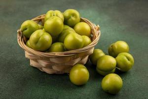 grüne Pflaumen im Korb auf grünem Hintergrund foto