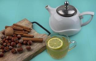 Tasse Tee mit Nüssen und Gewürzen auf blauem Hintergrund foto