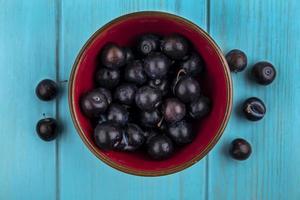 Beeren in einer Schüssel auf blauem Hintergrund