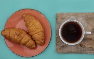Croissants und Tee auf Schneidebrett auf blauem Hintergrund