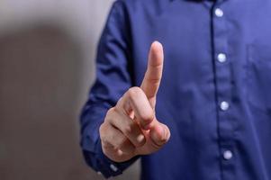 Geschäftsmann, der einen Finger in einem blauen Hemd zeigt