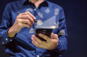 Geschäftsmann mit einem Smartphone und einem Stift, um Notizen zu machen foto