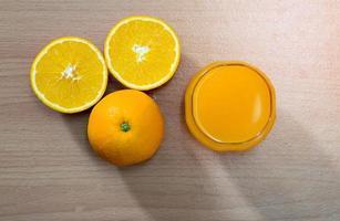 Draufsicht auf Orangen neben einem Glas Saft