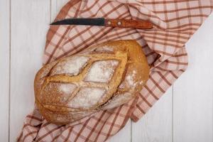 frisches Brot auf kariertem Stoff und hölzernem Hintergrund foto
