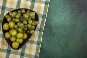 grüne Frucht in einer Schüssel auf kariertem Stoff und grünem Hintergrund foto