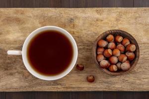 Tasse Tee mit Nüssen auf Holzschneidebrett