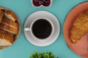 Tasse Tee mit Brot und Marmelade auf blauem Hintergrund