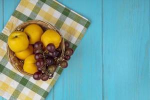 Frucht in einem Korb auf kariertem Stoff auf blauem Hintergrund mit Kopienraum