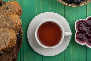 Tasse Tee mit Brot und Himbeermarmelade auf grünem Hintergrund