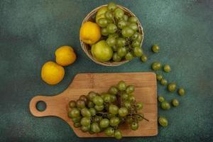 verschiedene Früchte auf Schneidebrett auf grünem Hintergrund