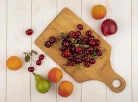 verschiedene Früchte auf Schneidebrett auf Holzhintergrund foto