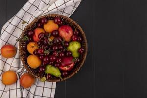 verschiedene Früchte auf dunklem Hintergrund mit kariertem Stoff
