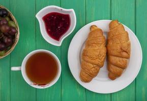 Croissants mit Marmelade und Tee auf grünem Hintergrund