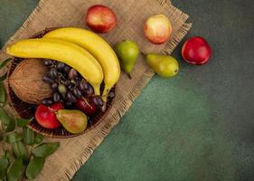 Draufsicht von Früchten in einem Korb auf Sackleinen und grünem Hintergrund foto