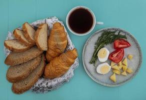 Frühstücksset mit Tee und Brot auf blauem Hintergrund