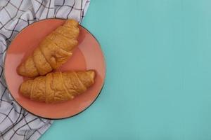 Croissants auf einem Teller auf blauem Hintergrund mit Kopierraum